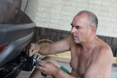 Mechanic installing hitch car Stock Photo