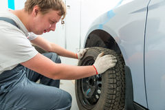 Mechanic installs on the car winter tires Royalty Free Stock Images