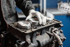 The mechanic installs a new piston. Disassemble engine block vehicle. Motor capital repair. Sixteen valves and four Royalty Free Stock Photography