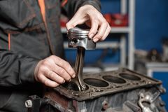 The mechanic installs a new piston. Disassemble engine block vehicle. Motor capital repair. Sixteen valves and four Royalty Free Stock Photo