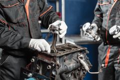 The mechanic installs a new piston. Disassemble engine block vehicle. Motor capital repair. Sixteen valves and four. Cylinder. Car service concept Royalty Free Stock Photos