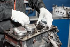 The mechanic installs a new piston. Disassemble engine block vehicle. Motor capital repair. Sixteen valves and four. Cylinder. Car service concept Stock Photography