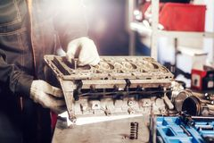 The mechanic installs a new valve. Disassemble engine block vehicle. Motor capital repair. Sixteen valves and four. Cylinder. Car service concept Stock Image