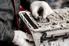 The mechanic installs a new valve. Disassemble engine block vehicle. Motor capital repair. Sixteen valves and four. Cylinder. Car service concept Royalty Free Stock Images