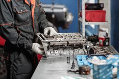 The mechanic installs a new valve. Disassemble engine block vehicle. Motor capital repair. Sixteen valves and four. Cylinder. Car service concept Stock Photo