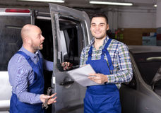 Mechanic and insurance agent at workshop Royalty Free Stock Image