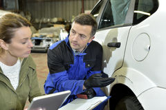 Mechanic and insurer discussing car reparations Royalty Free Stock Photography