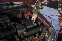 Mechanic jumper cables connected to a discharged battery. Firing the car in the winter by the jumper cables Royalty Free Stock Images