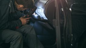 Mechanic with the lamp is checking inside the car in garage automobile service, close up stock footage