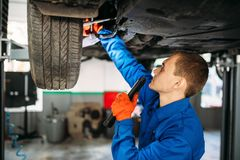 Mechanic with lamp checks the car suspension. Repair station. Tire service, vehicle maintenance royalty free stock images
