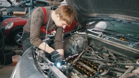 Mechanic with lamp repairs automotive engine, car repair, working in the workshop. Wide view stock footage