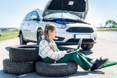 Mechanic with laptop diagnosing broken car stock photo
