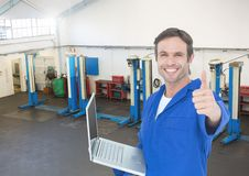 Mechanic with laptop showing thumbs up against garage in background. Digital composition of mechanic with laptop showing thumbs up against garage in background Royalty Free Stock Photography