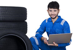 Mechanic with laptop and tires. Middle eastern mechanic smiling at the camera while holding laptop near a pile of tires,  on white background Stock Photo