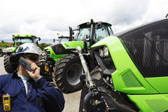 Mechanic and large farming tractors Stock Images