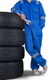 Mechanic lean on tires. Man wearing mechanic uniform and leans on a pile of tires while holding a wrench Stock Photo