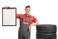Mechanic leaning on pile of tires and holding blank clipboard Stock Photo