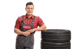 Mechanic leaning on a stack of tires. And looking at the camera isolated on white background Stock Photo