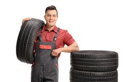 Mechanic leaning on a stack of tires. Isolated on white background Stock Images