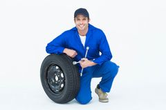 Mechanic leaning on tire while holding wheel wrenches Royalty Free Stock Photography