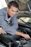 Mechanic looking at car engine. Adjust royalty free stock image