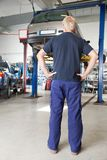 Mechanic looking at car. Rear view of mechanic looking at car in auto repair shop with hands on waist stock photo