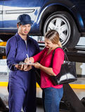 Mechanic Looking At Customer Signing Document Royalty Free Stock Photography