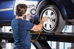 Mechanic Looking At Gauge While Inflating Car Tire. Rear view of male mechanic looking at gauge while inflating car tire at garage Royalty Free Stock Photo