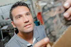 Mechanic looking for spare part. Mechanic looking for a spare part Royalty Free Stock Image
