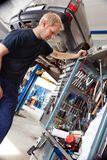 Mechanic Looking for Tool. Mechanic looking at his tools and equipmant in auto repair shop Royalty Free Stock Images