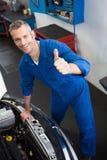 Mechanic looking up at camera. At the repair garage Stock Photos