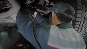 Professional automechanic is working on car troubles. Mechanic is loosening bolts being under the vehicle in a car maintenance service. He is working with stock video