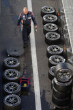 Mechanic and a lot of tyres Royalty Free Stock Images