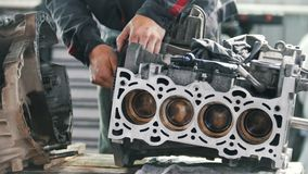 The mechanic lubricates the gear of the valve block of the car engine and repairs it. Close up stock video