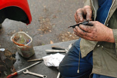 Mechanic lubricates new brake pad with copper oil. Royalty Free Stock Images