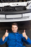 Mechanic lying and working under car. At the repair garage Stock Image