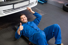 Mechanic lying and working under car. At the repair garage Stock Images