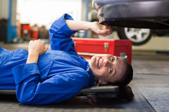 Mechanic lying and working under car Royalty Free Stock Photography