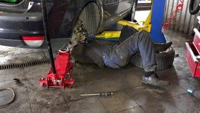 Mechanic lying and working under car at repair garage. Mechanic lying and working under car at the repair garage stock video footage