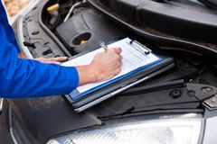 Mechanic maintaining car records Royalty Free Stock Photography