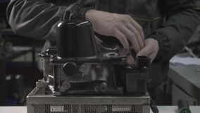 The mechanic makes dismantling of an automobile automatic transmission DSG7, gear shift, hydroaccumulator. The mechanic makes dismantling of an automobile stock video footage