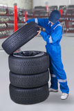 Mechanic makes a stack of tires. Image of a male mechanic makes a stack of tires while wearing uniform in the workshop Stock Photography