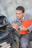 Mechanic making assessment damaged car stock image