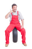 Mechanic making call us gesture resting on car wheel Royalty Free Stock Photography