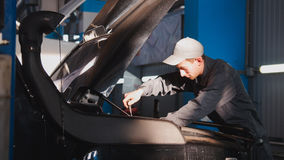Mechanic male unscrews with a screwdriver in hood of the car for SUV Stock Images