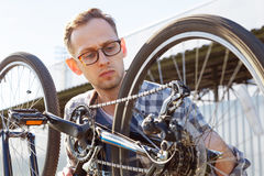 The mechanic man checks transmission system of the bicycle outdoor. Stock Images