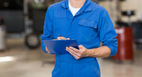 Mechanic man with clipboard at car workshop Royalty Free Stock Image