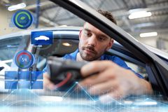 Mechanic man with diagnostic scanner at car shop. Service, repair, maintenance and people concept - mechanic man with automotive diagnostic scanner checking car stock photography
