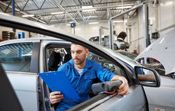 Mechanic man with diagnostic scanner at car shop. Service, repair, maintenance and people concept - mechanic man with automotive diagnostic scanner and clipboard royalty free stock photos