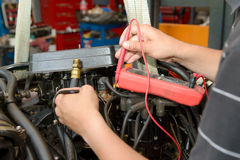 Mechanic man with digital multimeter testing ignition coil Royalty Free Stock Image